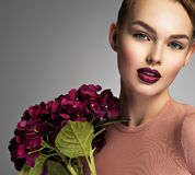 Girl with a creative hairstyle purple flowers. royalty free stock image
