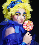 Girl with with creative make-up holds lollipop Stock Photo