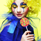 Girl with with creative make-up holds lollipop Stock Image