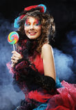 Girl with with creative make-up holds lollipop. Stock Image