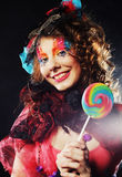 Girl with with creative make-up holds lollipop. Royalty Free Stock Photos