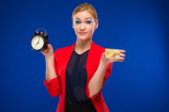 Girl with a credit card and an alarm clock in hands. On a blue background Stock Image