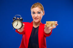 Girl with a credit card and an alarm clock in hands. On a blue background Royalty Free Stock Photography