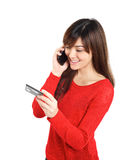 Girl with credit card on mobile phone Stock Photos