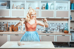 Girl cries in kitchen, her hands stuck to dough. Stock Photo