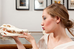 Girl with crocodile skull. Girl in white vintage dress sitting in front of butterflies and holding a skull of an crocodile stock photos