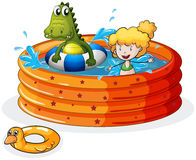 A girl and a crocodile swimming inside the inflatable pool Stock Images