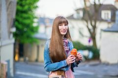 Girl with croissant on a street of Montmartre Royalty Free Stock Images