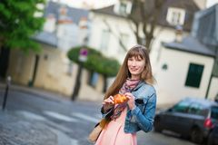 Girl with croissant on a street of Montmartre Stock Photos