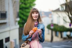 Girl with croissant on a street of Paris Royalty Free Stock Photo