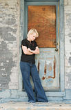 Girl with Crossed Arms. Portrait of a blond girl with with arms crossed standing by boarded door Royalty Free Stock Images