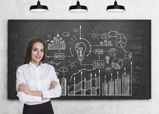 Girl with crossed arms and business idea. Portrait of a businesswoman standing with crossed arms near a blackboard with a business idea drawing on it stock image