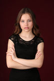 Girl with crossed arms. Close up. Dark red background Royalty Free Stock Photo
