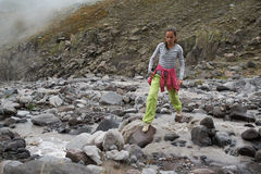 Girl is crossing mountain river Royalty Free Stock Photos