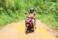 Girl crossing muddy pond on motorbike Royalty Free Stock Image