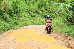 Girl crossing muddy pond on motorbike. Indonesian girl - young woman in blue helmet sitting on red motorbike crossing pond on muddy road in tropical jungle Royalty Free Stock Photography