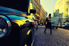 Girl crossing the road of stones between the cars in the city Stock Photography