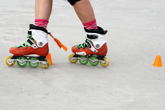 Girl crossing skates while skating. With cones Stock Photos