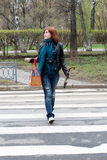 Girl crossing the street stock photography