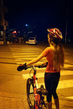 Girl is crossing  zebra crosswalk on bicycle at night city. Stock Images