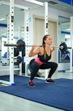 Girl crouches with a barbell. Stock Images