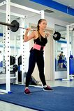 Girl crouches with a barbell. Stock Photography