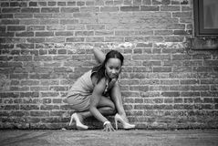 Girl crouching. Young girl crouching against brick wall in black and white Royalty Free Stock Images