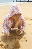 Girl crouching on the beach. Young girl in a flowery hooded top crouching on the sand at the beach Royalty Free Stock Images