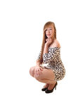 Girl crouching on floor. A pretty teenage girl in a short leopard print dress crouching on the floor Royalty Free Stock Photography