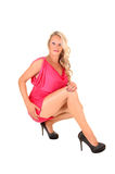 Girl crouching on floor. A lovely blond woman in a short pink dress crouching on the floor Stock Images