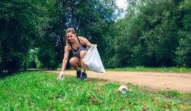 Girl with garbage bag doing plogging. Girl crouching with garbage bag doing plogging outdoors stock images