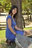 Girl crouching next to tree Stock Photo