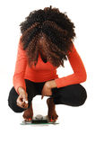 Girl crouching on scale. A lovely black teen girl crouching on a scale, looking on her little weight Stock Photography