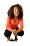 Girl crouching on scale. A lovely black teen girl crouching on a scale, looking into the camera Royalty Free Stock Photo