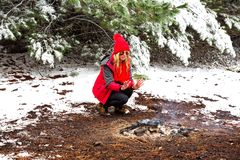 Girl crouching and warming frost bite hands in the smouldering fire. Female outdoors lifestyle crouching down by the fire warming stinging frost bitten hands in royalty free stock photography