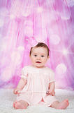 Girl with a crown, sitting on a pink background with bokeh. royalty free stock images
