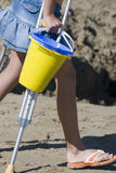 Girl on Crutches. Young girl at beach on crutches carrying sand pails Royalty Free Stock Photo
