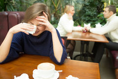 Girl crying on background happy couple. sitting in Royalty Free Stock Photo