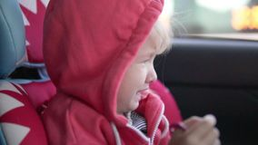 Girl crying in a car seat. Sad little girl rides in a car in the car seat stock video footage