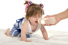 Girl crying while drinking milk. Adorable baby girl crying while drinking milk on a white background Stock Photography