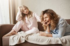 Girl crying her heart out of being lonely without couple. Beautiful european blonde in nightwear sitting on sofa royalty free stock image