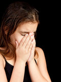 Girl crying and hiding her face. Emotional portrait of a girl crying and hiding her face isolated on black with space for text stock photos