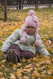 Girl crying on leaves. Girl crying on yellow leaves - autumn - green jacket - pink hat Royalty Free Stock Photo