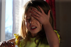 Girl crying at the window. Upset little girl crying at the window Royalty Free Stock Photos