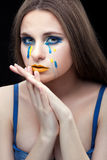 Girl crying yellow blue tears. Stock Photography