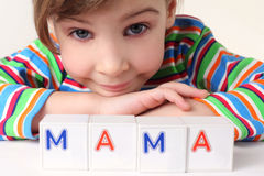 Girl with cubes, puts it together in word mother Stock Image