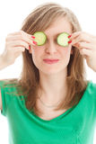 Girl with a cucumber. Woman with slice of cucumbers in her eyes Royalty Free Stock Photo