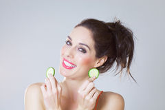 Girl With Cucumber Slices. Happy fresh girl with cucumber slices over studio background Stock Photos