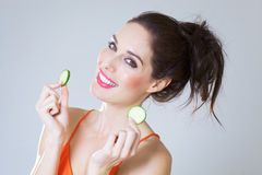 Girl With Cucumber Slices. Happy fresh girl with cucumber slices over studio background Royalty Free Stock Photo