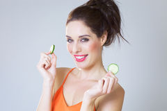 Girl With Cucumber Slices. Happy fresh girl with cucumber slices over studio background Royalty Free Stock Photos